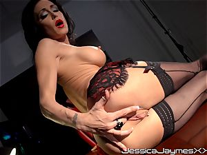 kinky brown-haired Jessica Jaymes thumbs her tastey cunt pie in her office